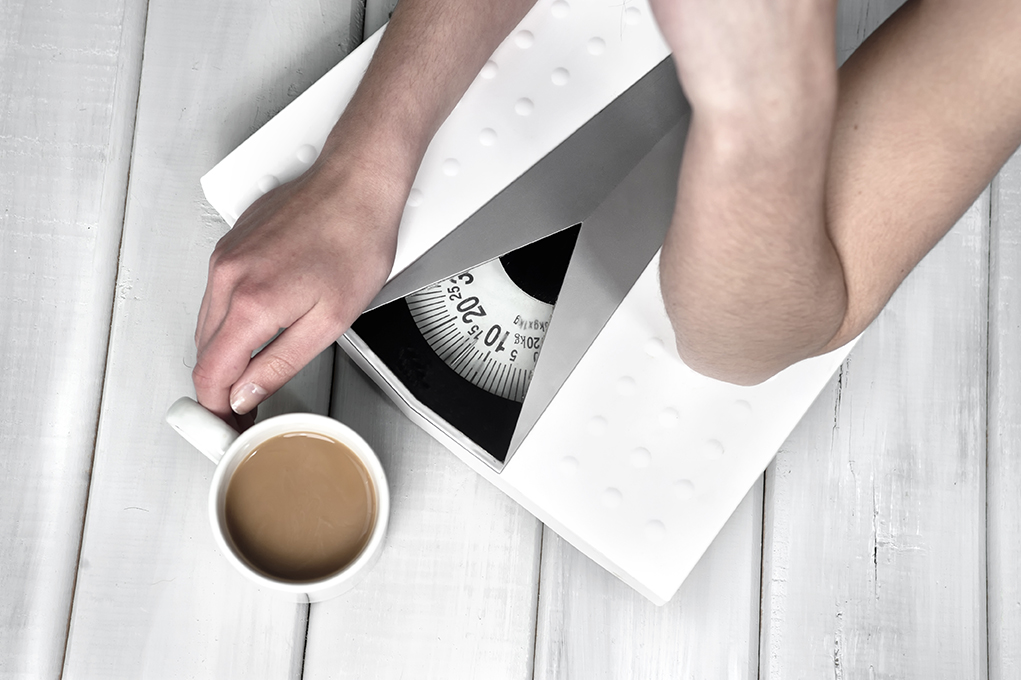 Hands close up of a woman lying on weight scale drinking coffee