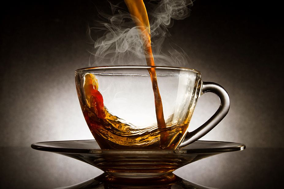 Pour coffee into transparent glass with steam cup on dark background.